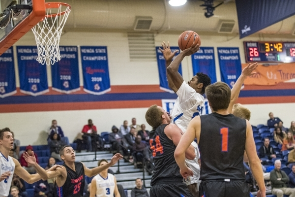 Bishop Gorman guard Christian Popoola Jr. (22) takes a shot while being defended by Timpview ...