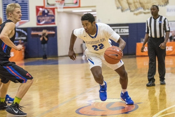 Bishop Gorman guard Christian Popoola Jr. (22) drives to the basket while being defended by ...