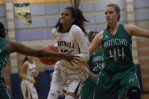 Foothillís Rae Burrell (12) works the ball toward the basket as Rancho's Samantha P ...