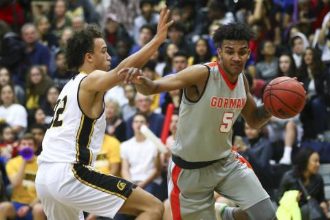 Bishop Gorman's Jamal Bey (5) drives against Clark's Ian Alexander (32) during a ...