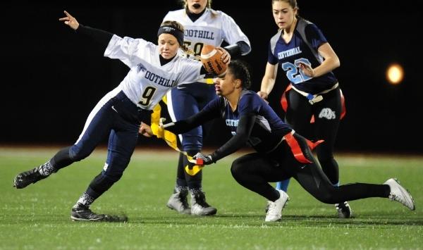 Centennial safety Kayla Kipp-Nobles, right, pulls the flag off of Foothill quarterback Jadyn ...