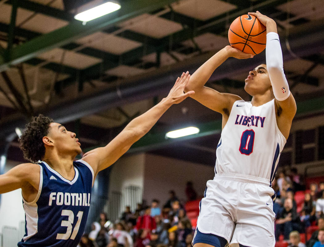 Liberty's Julian Strawther (0) goes up for a shot while Foothill's Marvin Colema ...