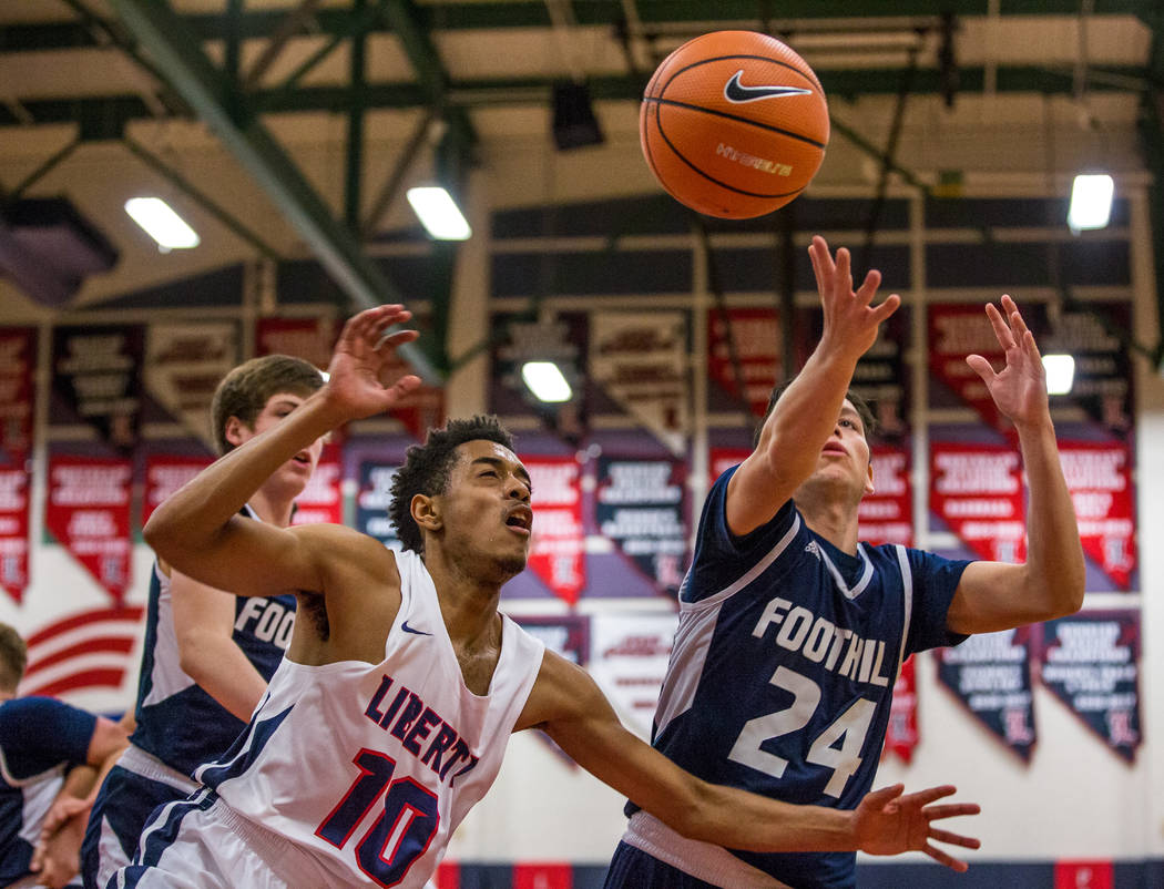 Liberty's Jordan Holt (10) and Foothill's Anthony Martin (24) grapple over the b ...