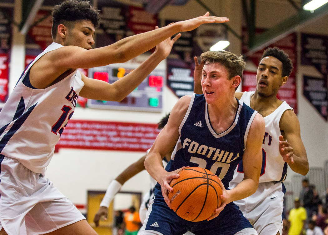 Foothill's Caleb Stearman (20) tries to get the ball away from Liberty defenders Jorda ...