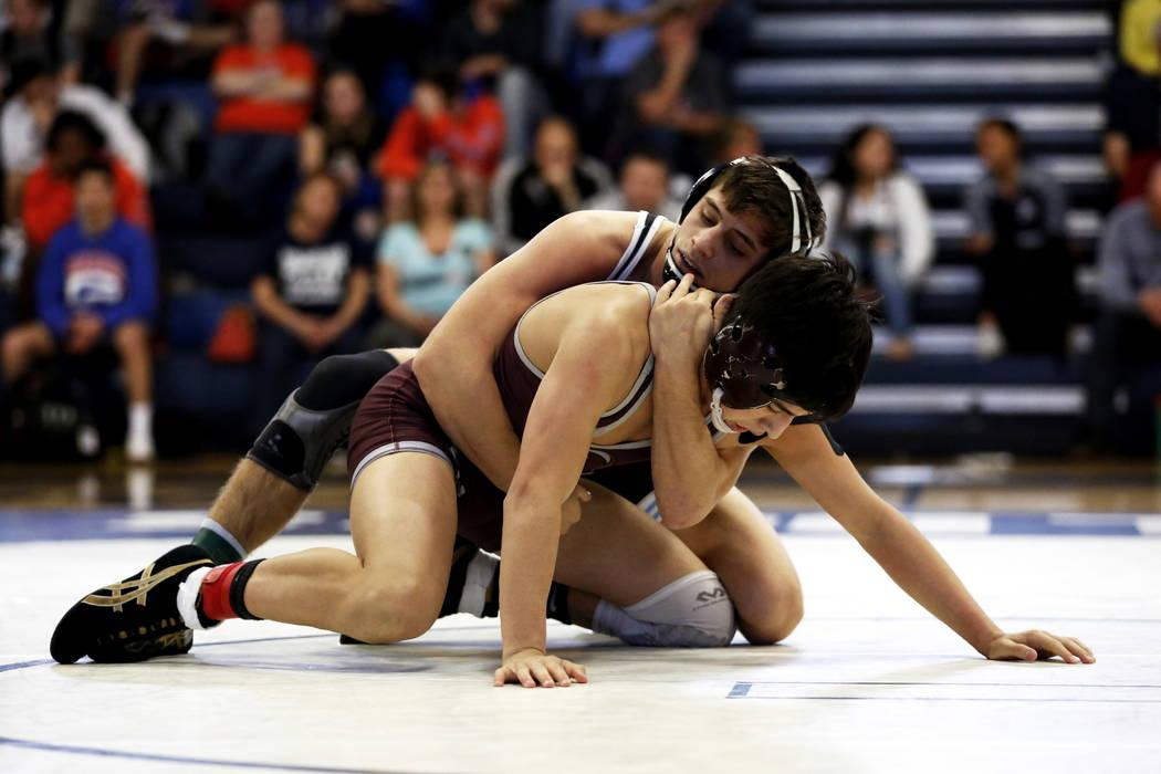 Nico Antuna, of Centennial High School, tries to pin Daniel Rodriguez, of Cimarron-Memorial ...