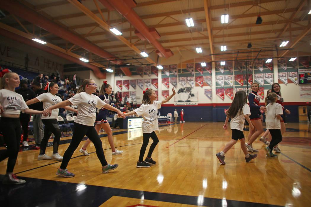 Coronado High School cheerleaders lead young cheerleaders-in-training to perform during half ...