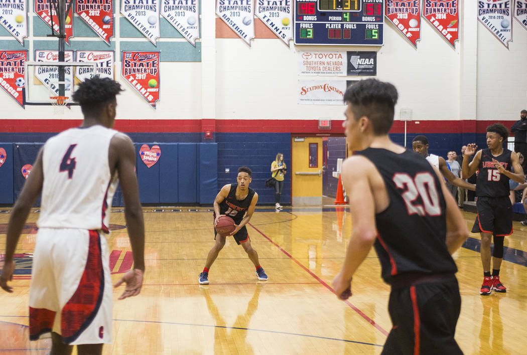 Liberty High School's Jordon Holt (10) prepares to dribble past opponents in a game ag ...