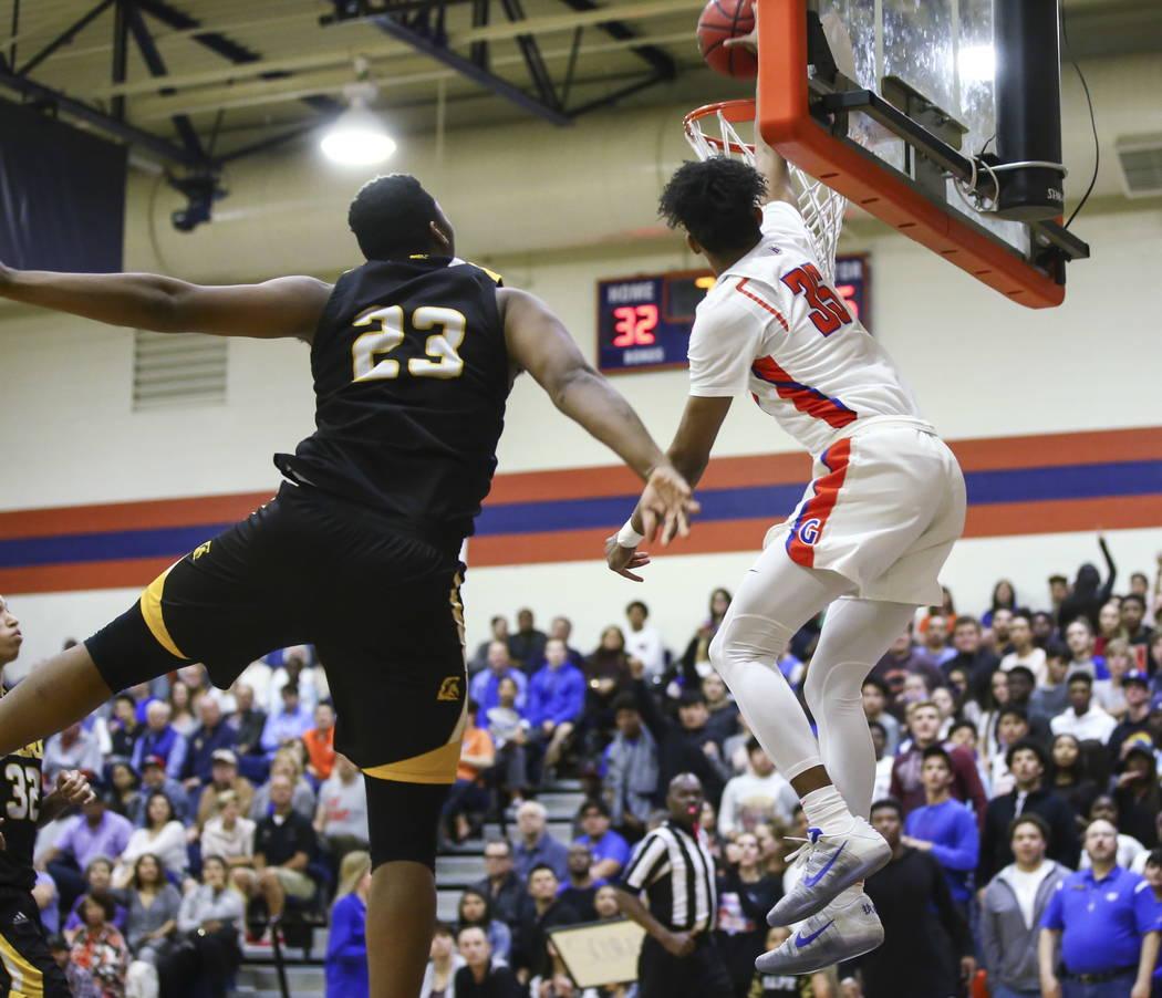 Bishop Gorman's Jamal Bey (35) attempts a dunk past Clark's Antwon Jackson (23) ...
