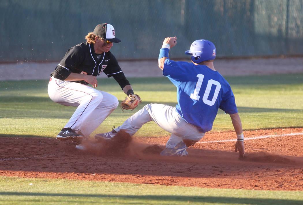 Green Valley baserunner Carter Gehlken (10) slides safely into third base under the tag of Z ...