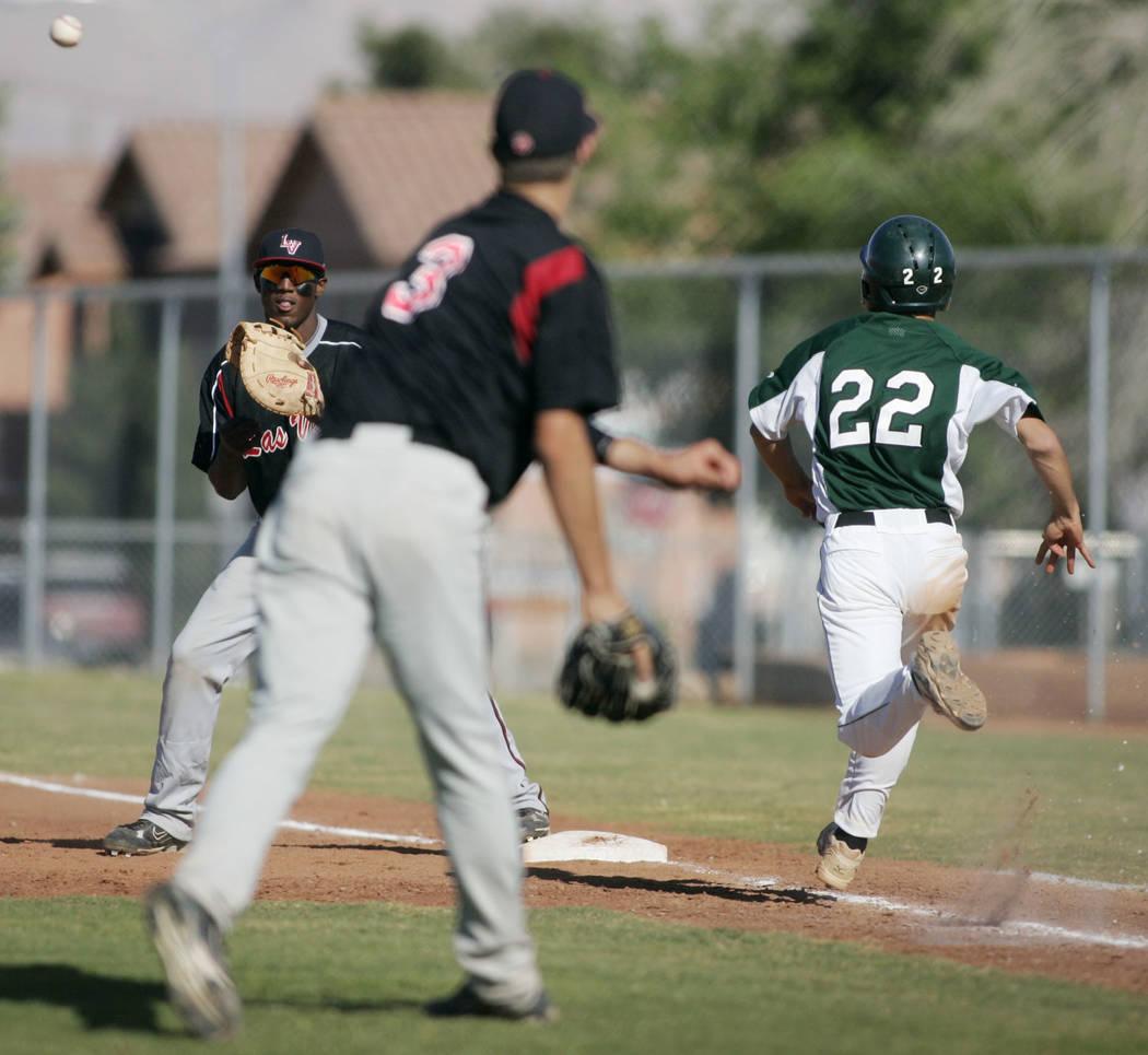 Las Vegas High School baseball player Bryan Harper throws to first baseman Marvin Campbell f ...