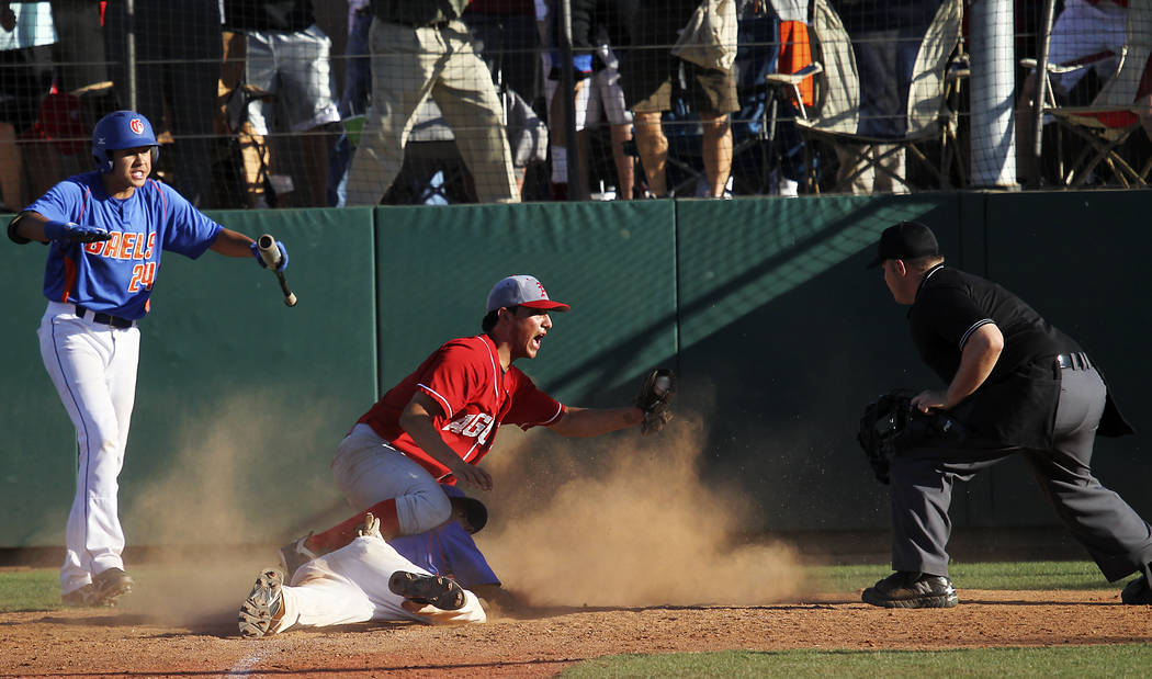 Arbor View's Zach Quintana shows the ball to the umpire after tagging out Bishop Gorma ...