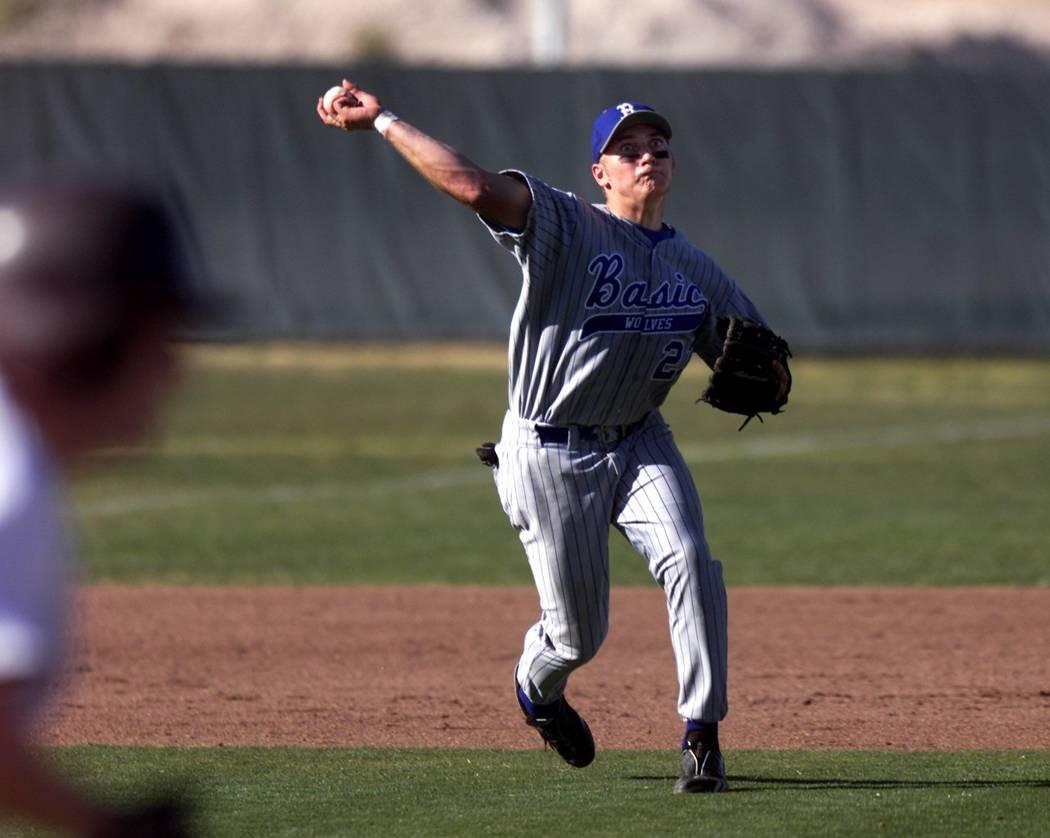 Basic High School third baseman Micah Schnurstein throws to first base during a game against ...
