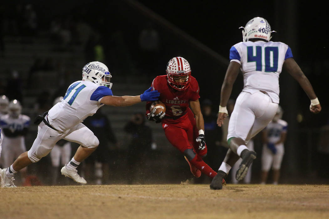 Liberty player Cervontes White (6) runs the ball during the class 4A Sunrise Region title ga ...