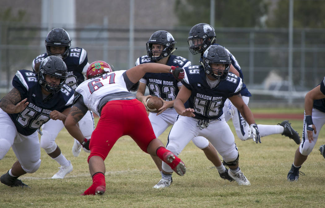 Shadow Ridge quarterback Kody Presser (33) looks for the hand off during a football game aga ...