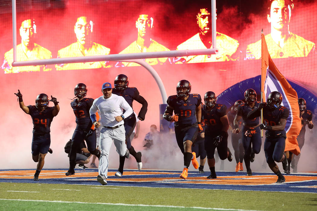 Bishop Gorman head coach Kenny Sanchez runs onto the field with his players prior to the sta ...