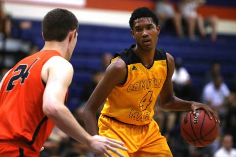 Compton Magic's Evan Mobley (4) attempts to pass Bishop Gorman's Myles Bendavid ...