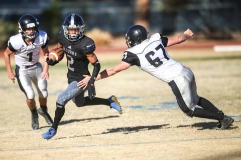 Desert Pines' Tye Moore (2), center, runs the ball past Spring Creek's Andrew Ar ...