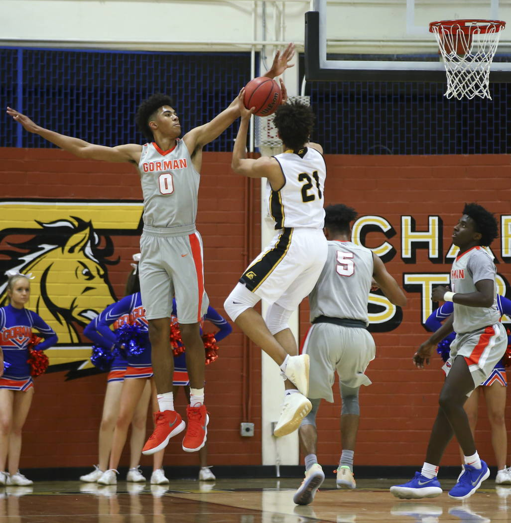 Clark's Jalen Hill (21) goes up to shoot as Bishop Gorman's Isaiah Cottrell (0) ...