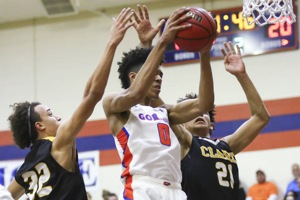 Bishop Gorman's Isaiah Cottrell (0) gets a rebound over Clark's Ian Alexander (3 ...