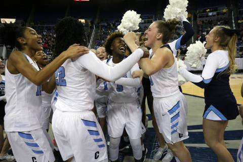The Centennial Bulldogs celebrate a 74-65 overtime win over Liberty for the NIAA state baske ...