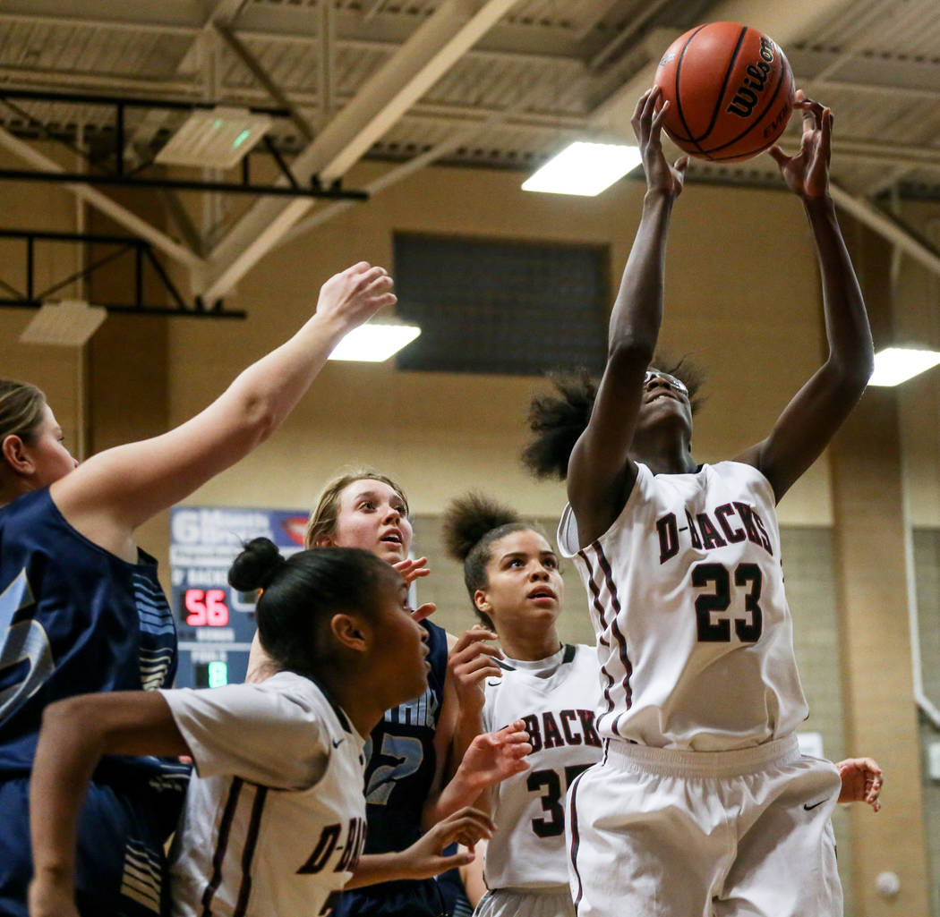 Desert Oasis' Desi-rae Young (23), right, catches a rebound during the fourth quarter ...