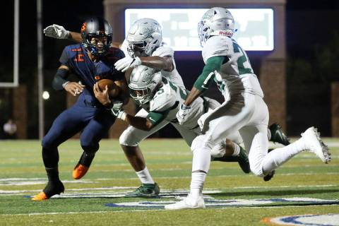 Bishop Gorman's Dorian Thompson-Robinson (14) runs the ball as he avoids tackles from ...