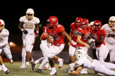 Arbor View player Kyle Graham run the ball as Faith Lutheran attempts to tackle during the ...