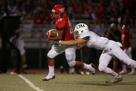 Arbor View player Kyle Graham (25) attempts to run the ball as Faith Lutheran player Keagan ...