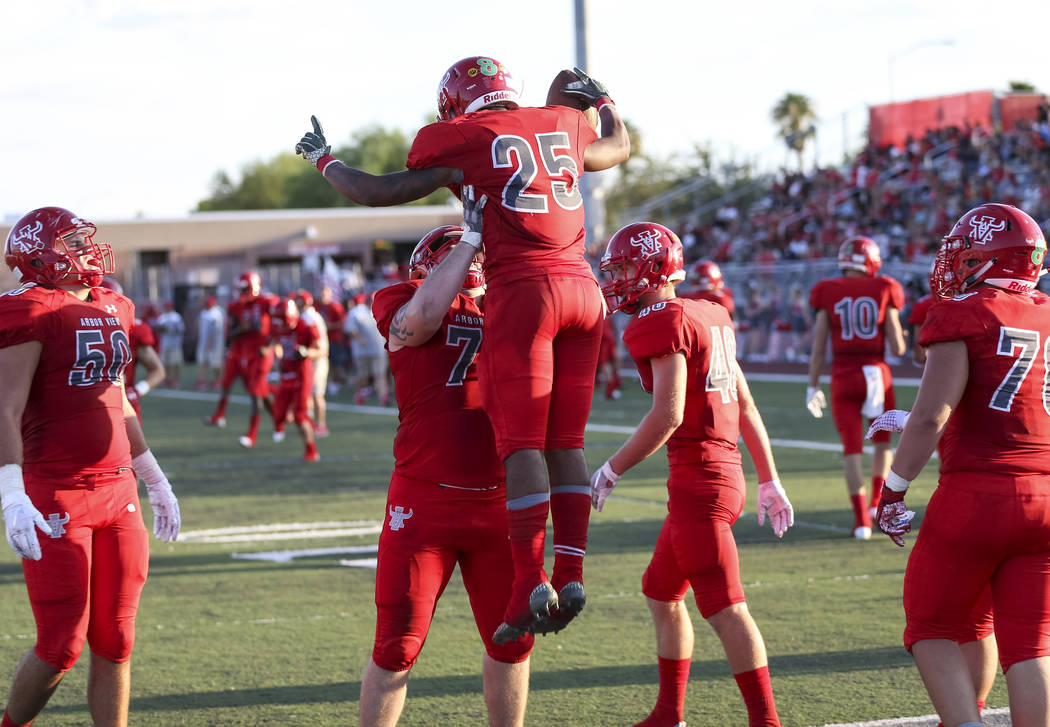 Arbor View Aggies running back Kyle Graham (25) celebrates with teammates after scoring a to ...