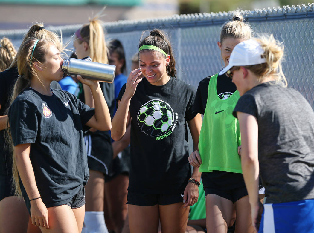Green Valley's Taylor O'Neill, 17, laughs with her teammates as they take a wate ...