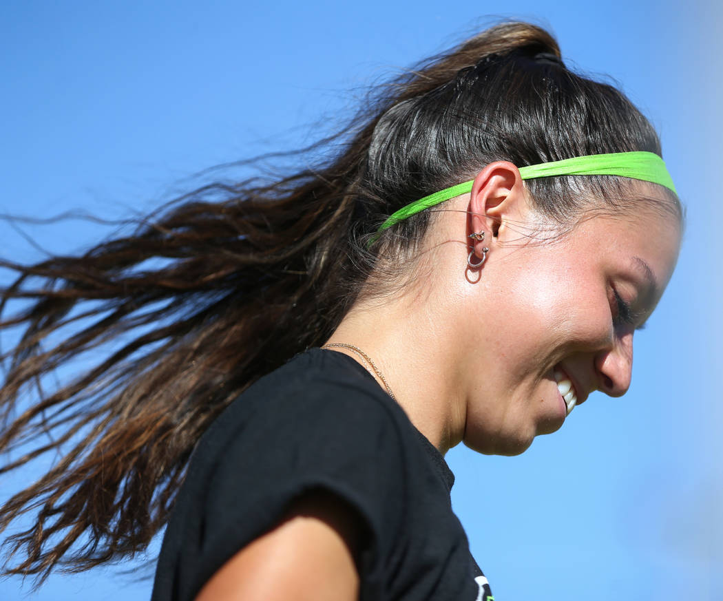Green Valley's Taylor O'Neill, 17, smiles as she looks down to grab a ball durin ...