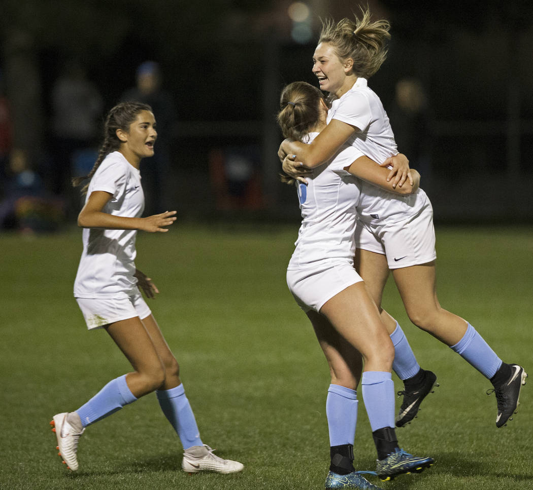 Foothill's Annalise Huber (19) and Aqui Williams (13) embrace after the Falcons scored ...