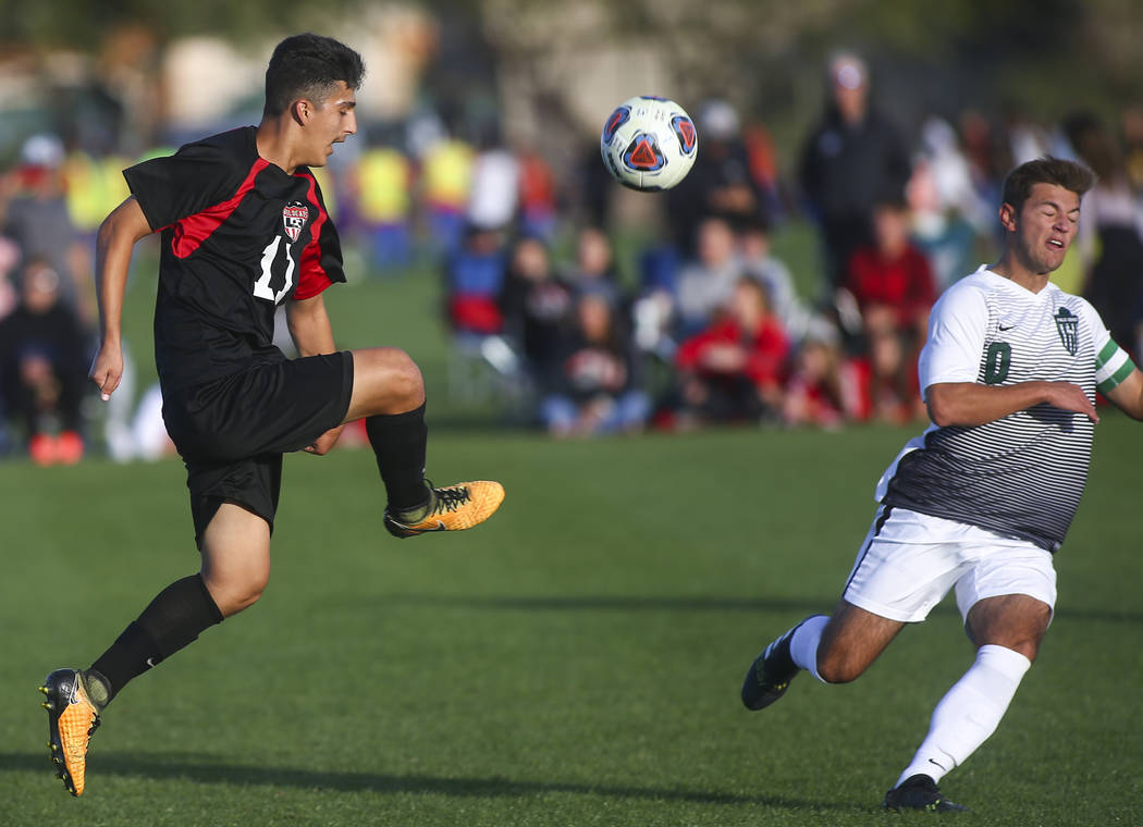 Las Vegas' Rigo Carrasco (11) kicks the ball past Palo Verde's Anthony Kaskie (1 ...