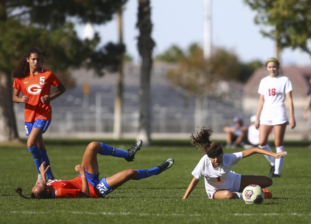 Bishop Gorman's Kennedy Enus (22) gets tripped up next to Coronado's Rachel Burt ...