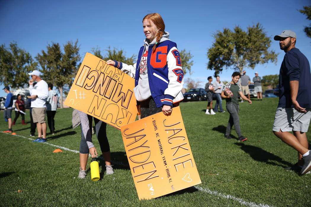 Bishop Gorman junior Sara Gillett, 16, carries signs in support of runners competing in the ...