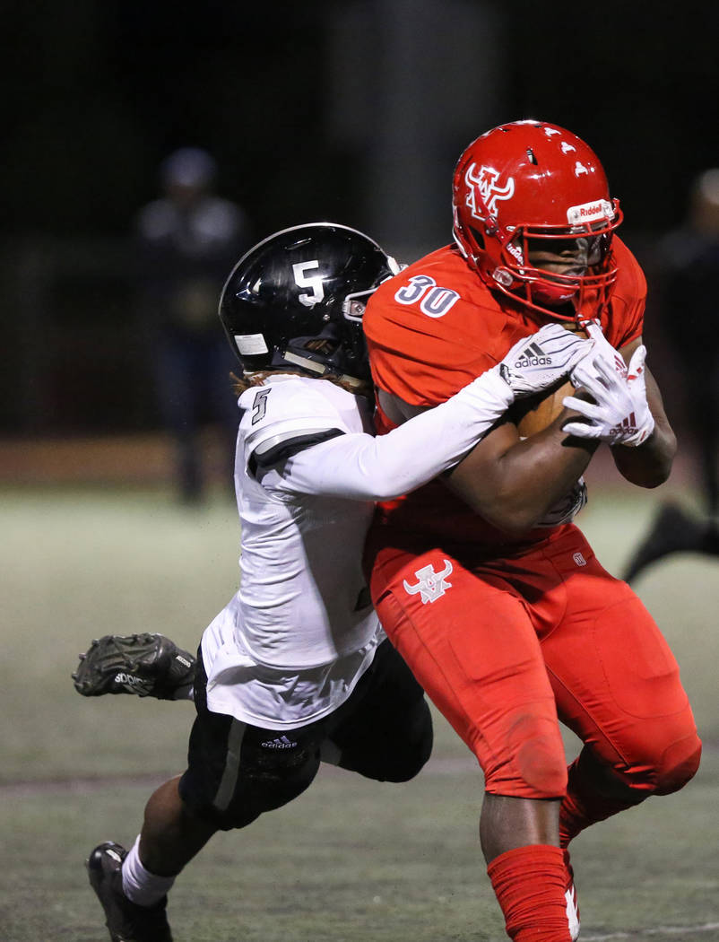 Arbor View's Darius Williams (30) protects the ball while being tackled by Desert Pine ...
