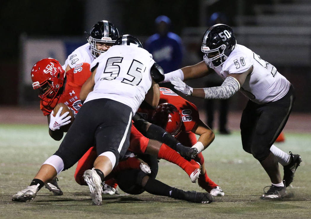 Arbor View's Darius Williams (30) gets tackled while in possession of the ball during ...