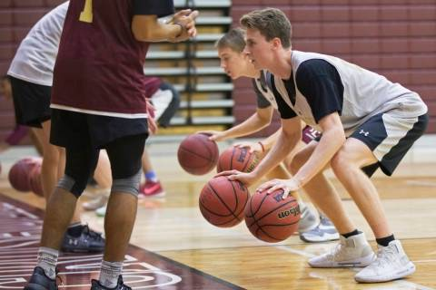 Faith Lutheran senior guard Brevin Walter, right, works through a dribbling drill during pra ...