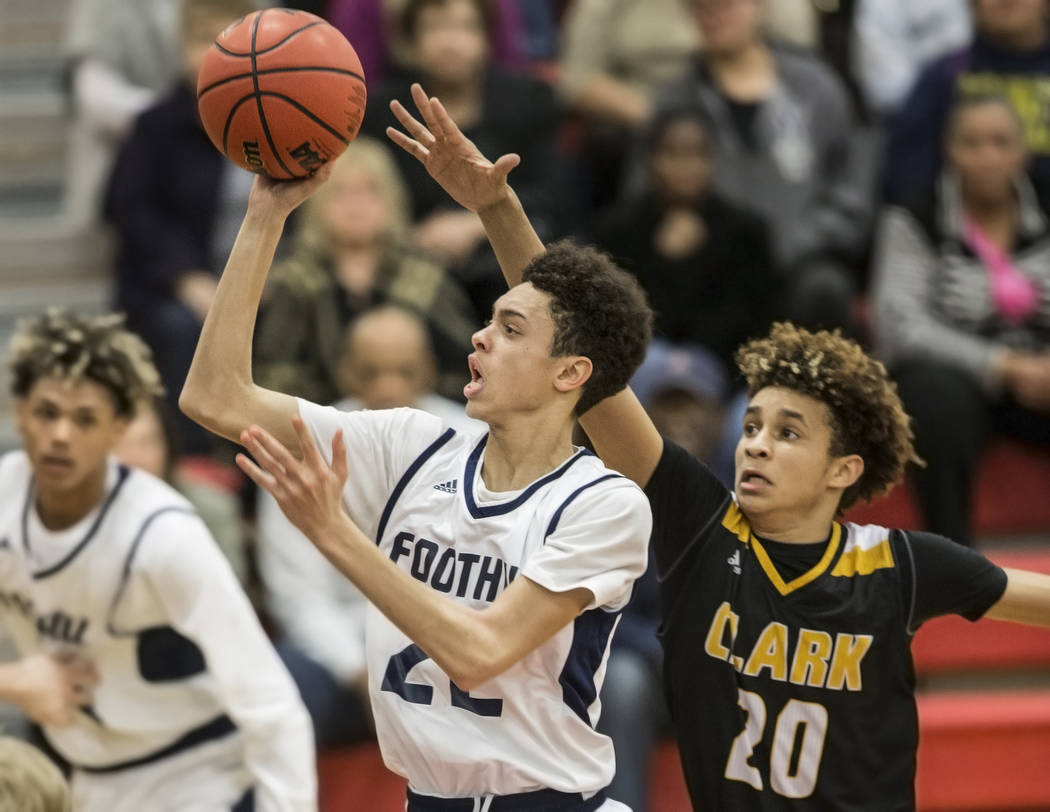 Foothill's Jace Roquemore (22) slices to the rim past Clark's Adam Forbes (20) ...