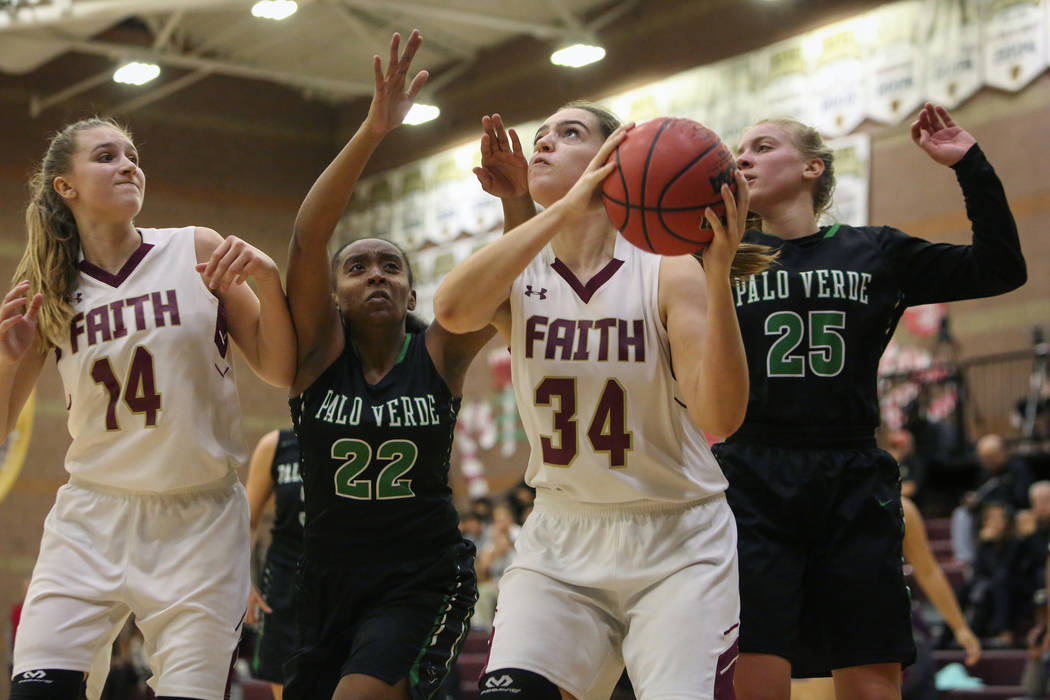 Faith Lutheran's Kelsey Howryla (34) looks to shoot the ball while under pressure from ...