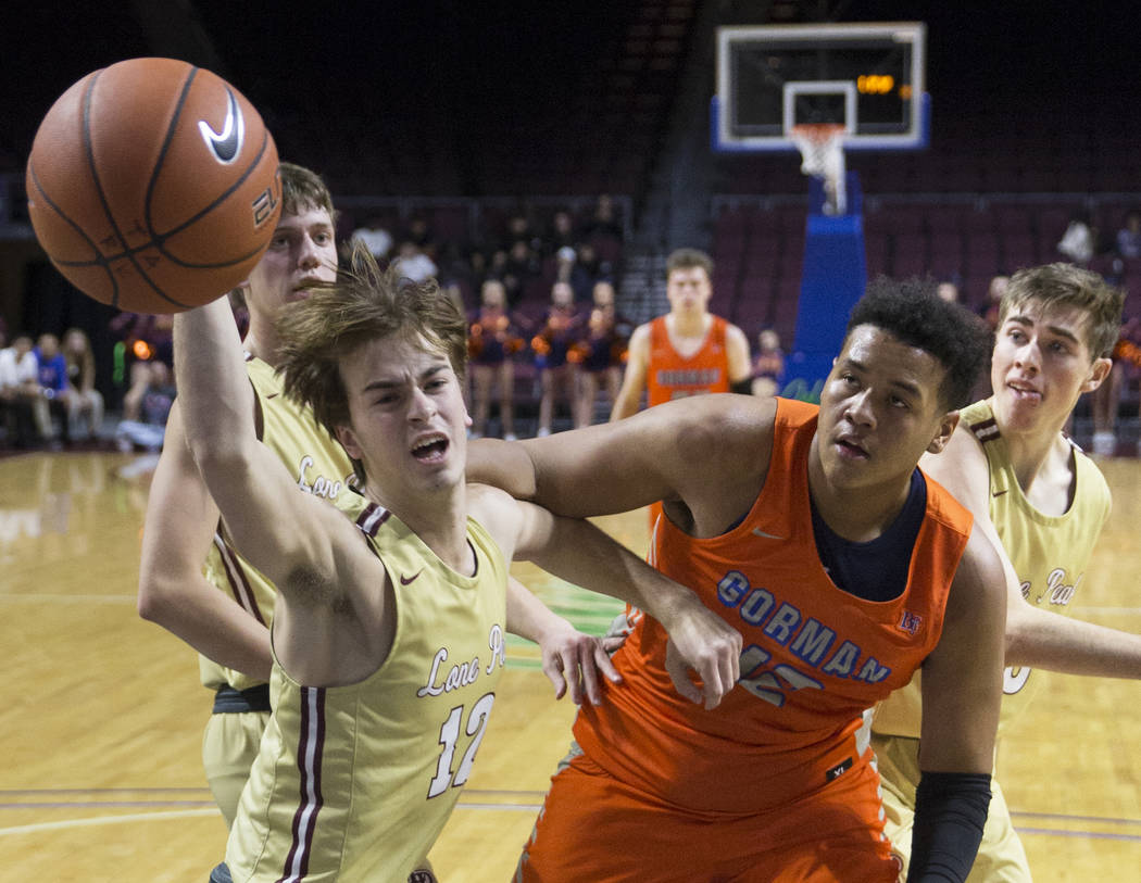 Bishop Gorman freshman forward Max Allen (12) fights for a loose ball with Lone Peak senior ...
