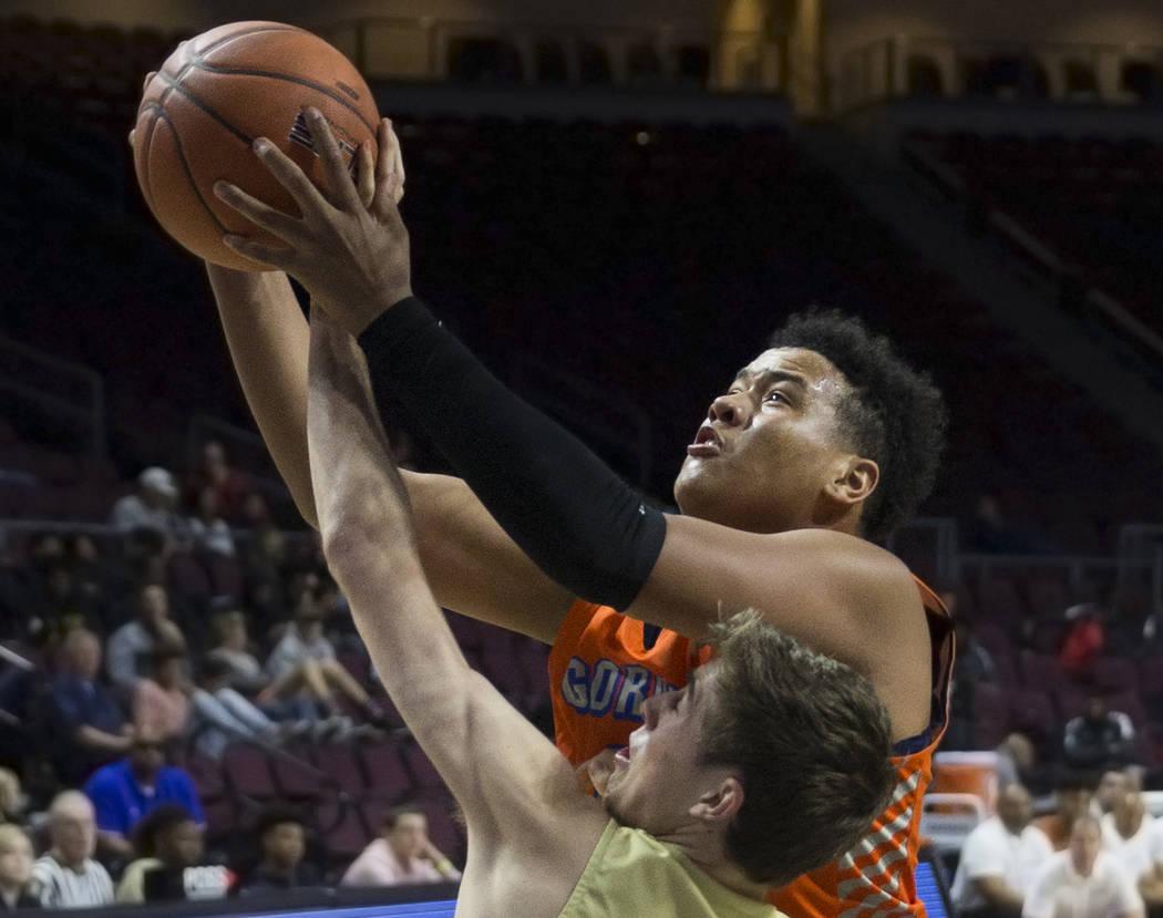 Bishop Gorman freshman forward Max Allen (12) grabs a rebound over Lone Peak senior guard Se ...