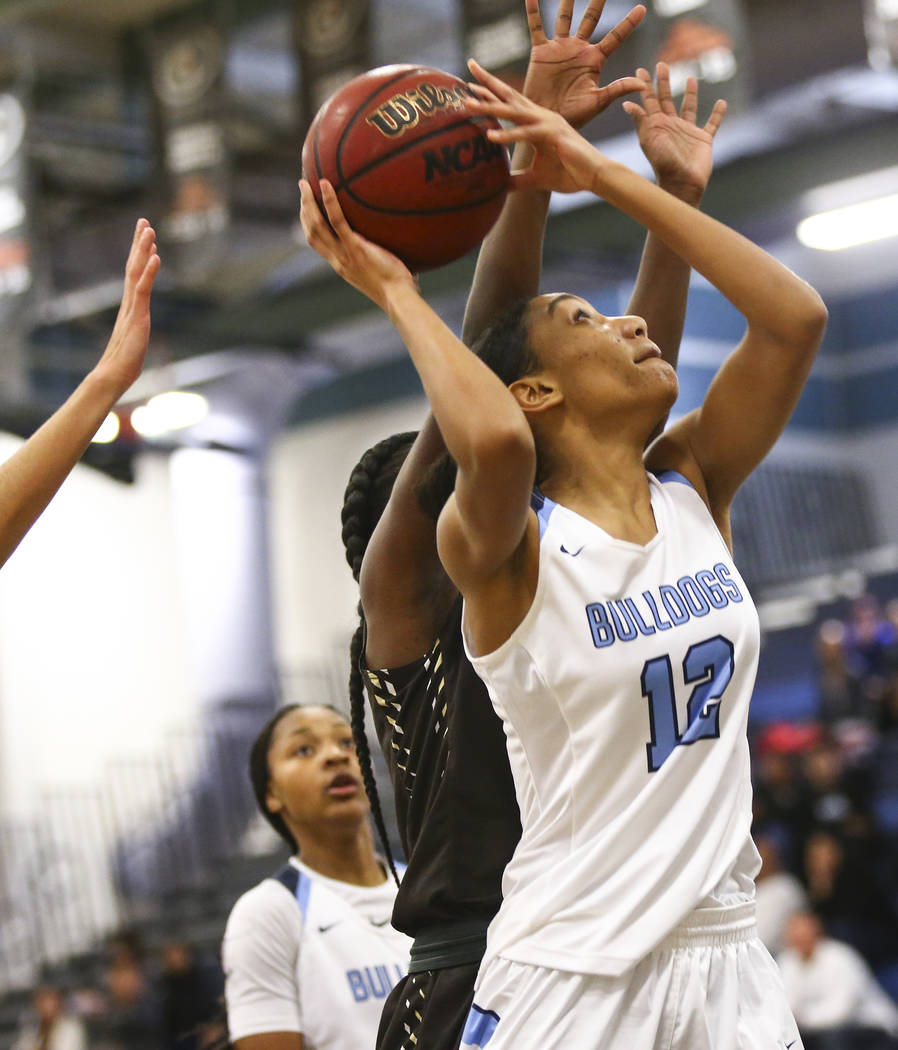 Centennial's Aishah Brown (12) looks to shoot against West during a basketball game at ...