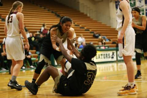 Spring Valley's Chyna Charles (33) gets help getting up from Chelsea Camara (5) after ...