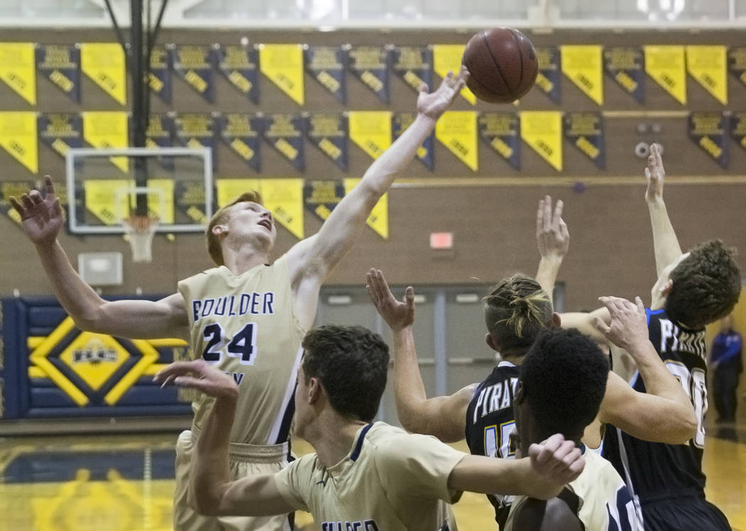 Boulder City sophomore guard Matt Morton (24) fights for a loose ball with Moapa Valley seni ...