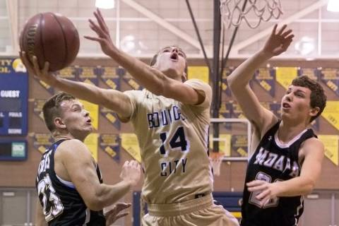 Boulder City senior guard Karson Bailey (14) slices to the rim past Moapa Valley sophomore f ...