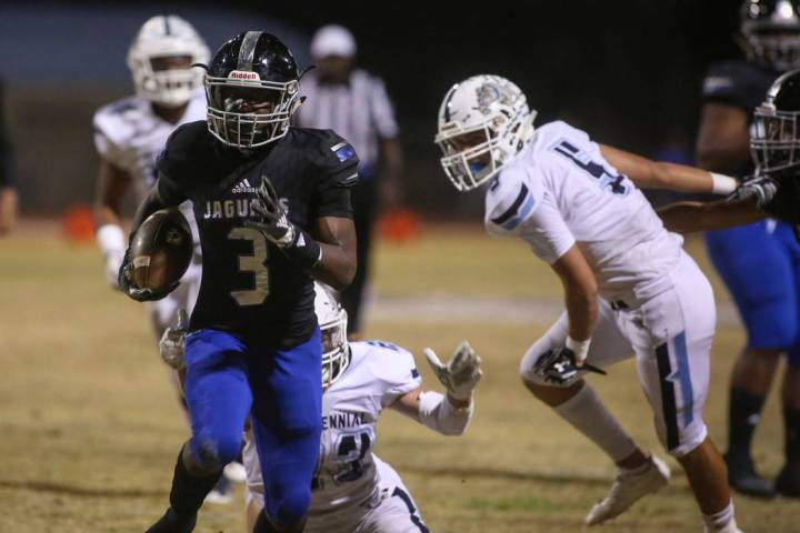 Desert Pines High School's Jamel Brown (3) runs with the ball after dodging a tackle f ...