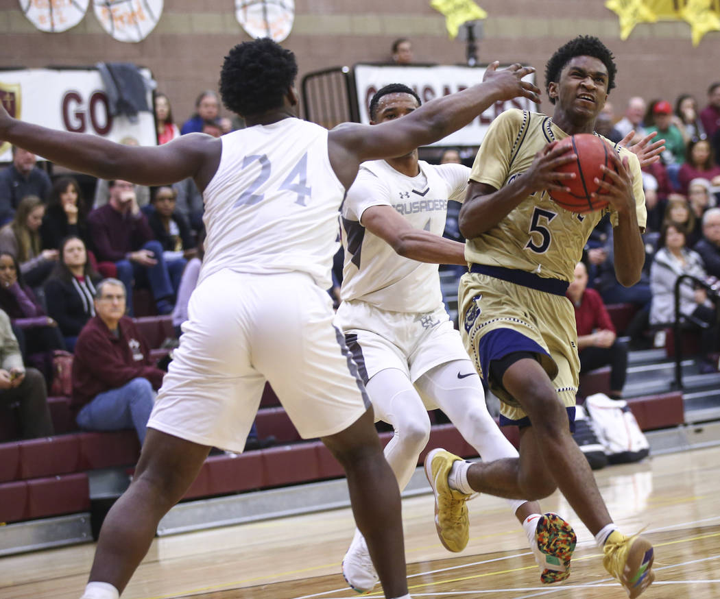 Cheyenne's Glenn Taylor (5) drives to the basket past Faith Lutheran's D.J. Heck ...