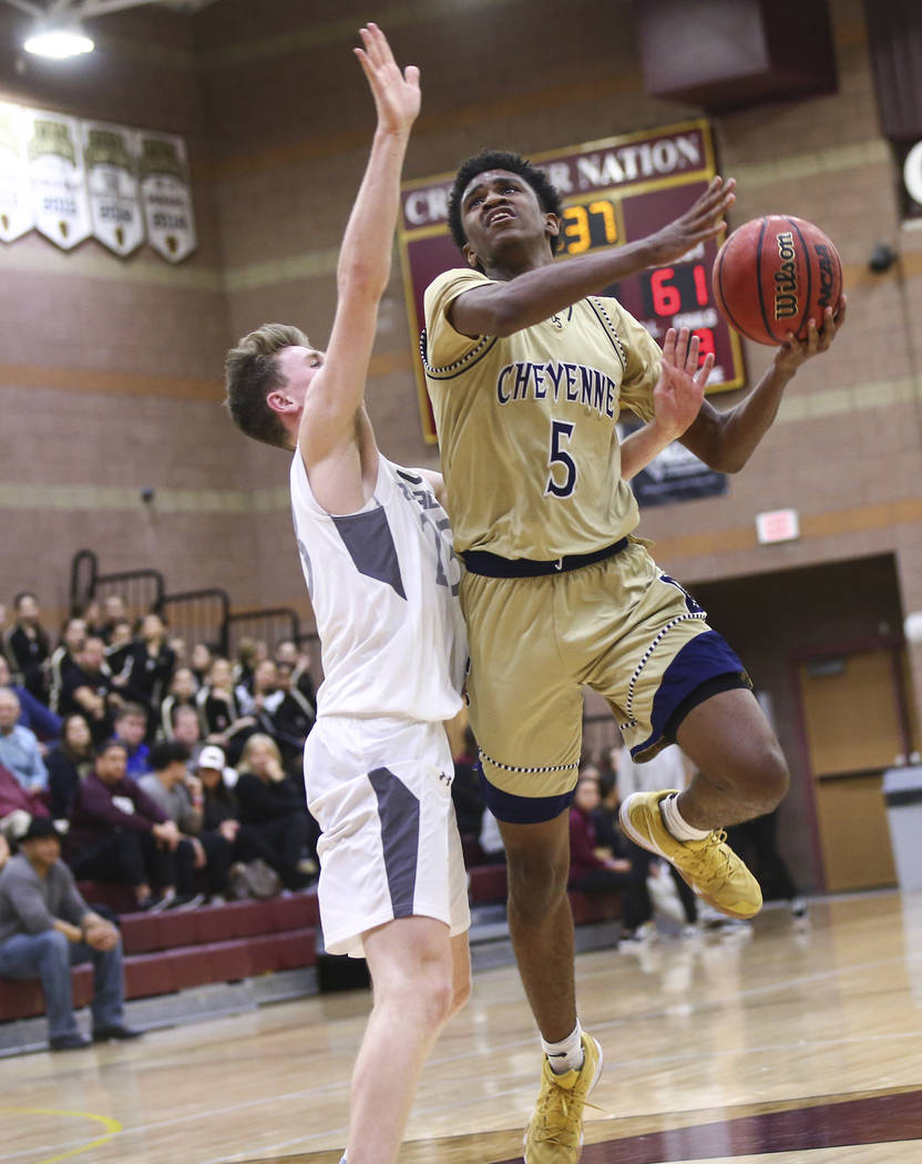 Cheyenne's Glenn Taylor (5) mvoes the ball around Faith Lutheran's Brevin Walter ...