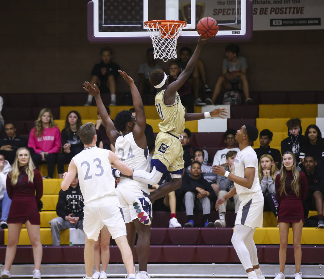 Cheyenne's Tommie Lindsey (11) goes to the basket past Faith Lutheran's D.J. Hec ...